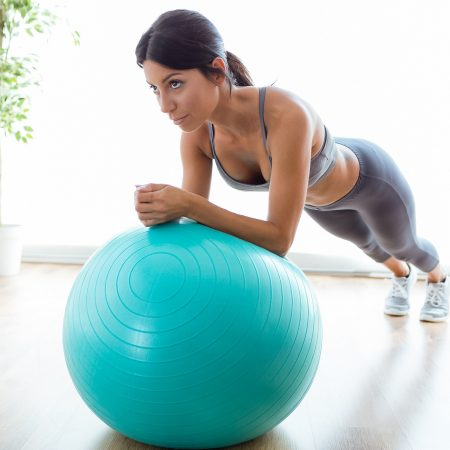 Beautiful young woman doing pilate exercise with fitness ball at